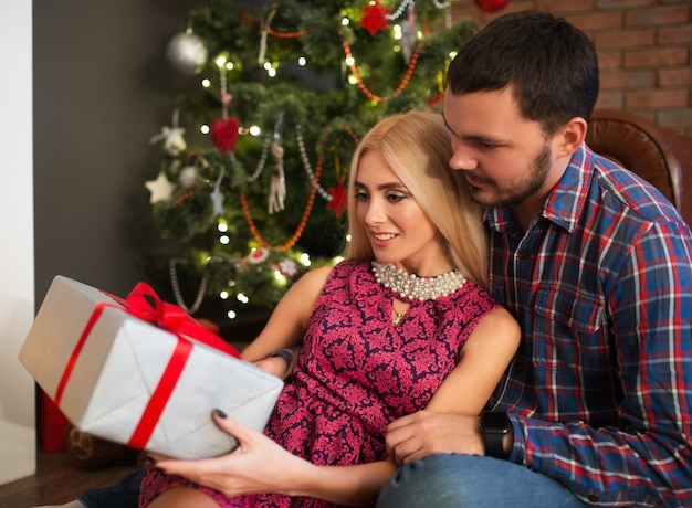 Schönes junges paar ein charmantes mädchen und ein mann, der eine schachtel mit einem geschenk hält