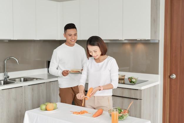 Schönes junges paar füttert sich und lächelt beim kochen in der küche zu hause