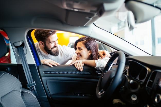 Schönes junges paar im autohaus, das ein neues auto zum kauf wählt.