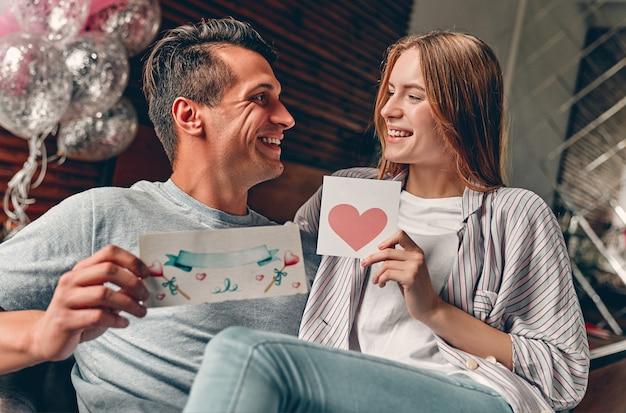 Schönes junges paar im schlafzimmer mit valentinsgrüßen in den händen. valentinstag feiern.