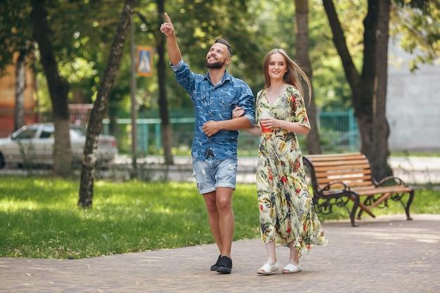 Schönes junges paar in der liebe, die im sommerpark mit kalter limonade geht. romantisches paar bei einem date an der frischen luft
