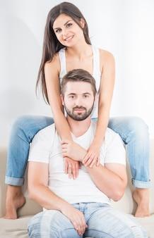Schönes junges paar kleidete das zufällige sitzen auf dem sofa.