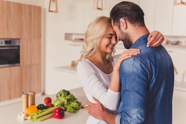 Schönes junges paar lächelt beim umarmen in der küche.