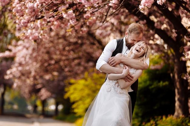 Schönes junges paar, mann mit bart und blonde frau, die im frühlingspark umarmen. stilvolles paar nahe dem baum mit sakura. konzeptfeder. mode und schönheit