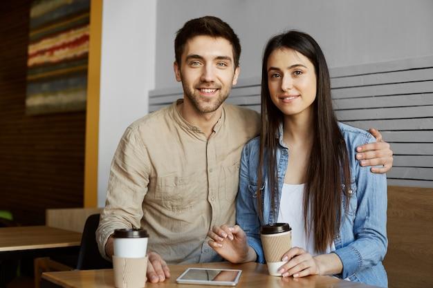 Schönes junges paar mit dunklem haar in freizeitkleidung lächelt, trinkt kaffee und posiert für foto im universitätsartikel über perspektivisches startprojekt.