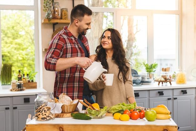 Schönes junges paar spricht, lächelt, während es tee oder kaffee isst und in der küche zu hause trinkt.