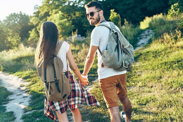 Schönes junges paar touristen, die händchen halten und lächeln, während sie im freien spazieren gehen