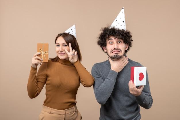 Schönes junges paar tragen neujahrshutmädchen mit geschenk, das siegesgeste angespannten kerl mit herz auf grau macht
