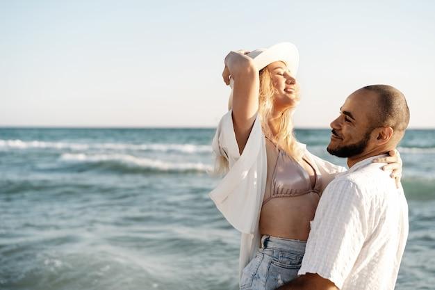 Schönes junges paar umarmt am strand am wasser, nahaufnahme