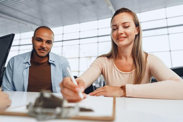 Schönes junges paar unterschreibt dokumente am autohausausstellungsraum, der am tisch sitzt