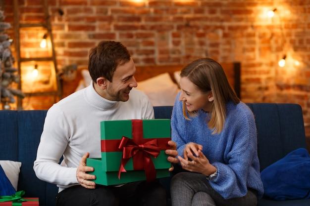Schönes junges paar zu hause, das ausgaben genießt