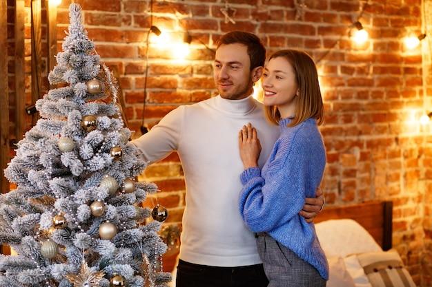 Schönes junges paar zu hause, das einen weihnachtsbaum verziert.