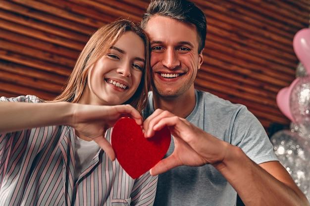 Schönes junges paar zu hause. ein verliebtes paar, das ein herz in den händen hält, während es den valentinstag feiert.