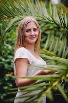 Schönes, junges, schlankes, langhaariges blondes mädchen im weißen langen kleid gegen palmen und natur. truthahn. modell stilvoll. mode. lächelt. glücklich. nahansicht