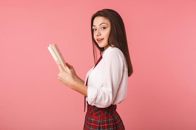 Schönes junges schulmädchen, das uniform trägt, die lokal über rosa wand steht