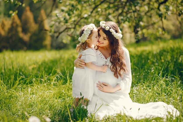 Schönes junges schwangeres mädchen in einem langen weißen kleid, das mit kleinem mädchen spielt