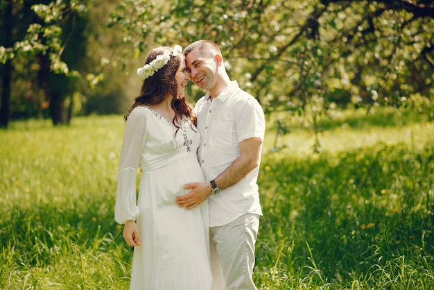 Schönes junges schwangeres mädchen in einem langen weißen kleid mit ihrem freund