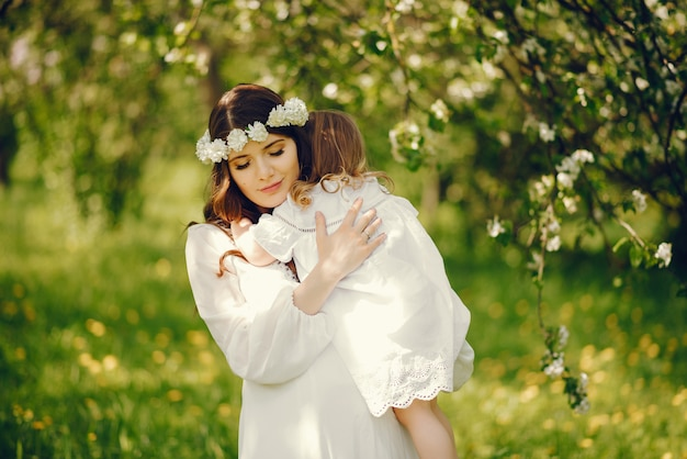 Schönes junges schwangeres mädchen in einem langen weißen kleid mit kleinem mädchen in ihren armen