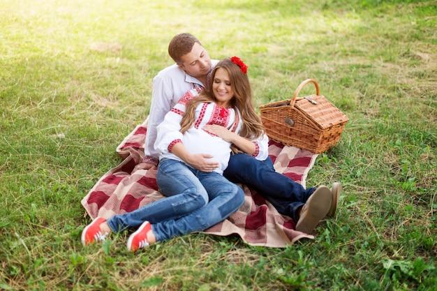 Schönes junges schwangeres paar gekleidet im nationalen ukrainischen stil, der picknick im herbstpark hat. mutterschafts- und familienglückskonzept.
