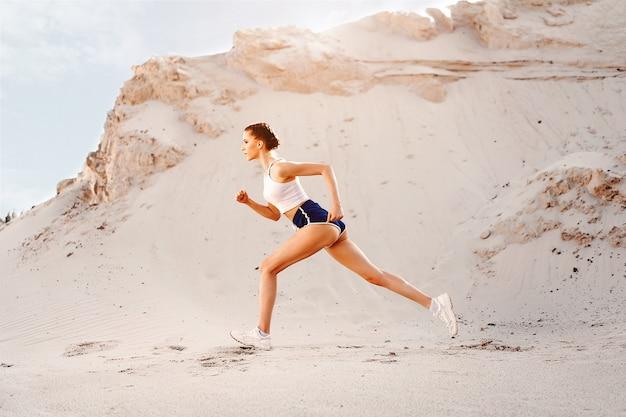 Schönes junges sexy athletisches mädchen, das auf dem natursommermorgen läuft. frau trainieren in der nähe des sees. gesunder lebensstil. fitnesstraining im freien.