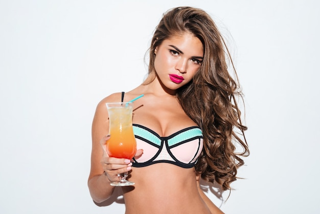 Schönes junges sexy mädchen, das cocktail trägt bikini lokalisiert auf dem weißen hintergrund hält