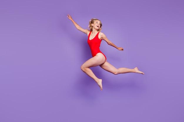 Schönes junges sorgloses modell mit blondem haar, das auf purpur fliegt