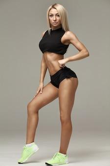 Schönes junges sportliches fitnessmodellmädchen, das im studio auf grauem hintergrund aufwirft