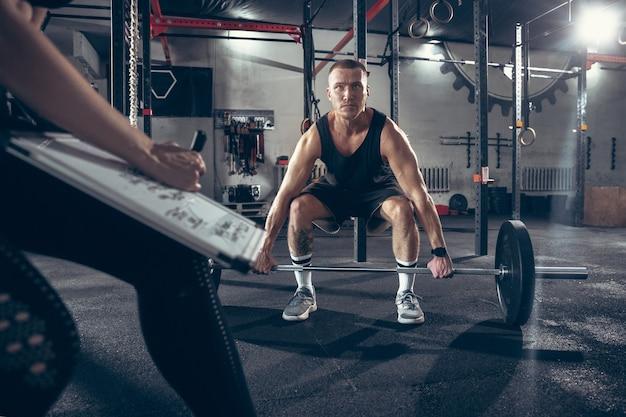 Schönes junges sportliches paar, das zusammen im fitnessstudio trainiert
