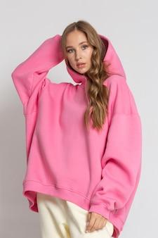 Schönes junges sportmädchen, das die kapuze ihres rosa hoodies auf dem weißen hintergrund anzieht