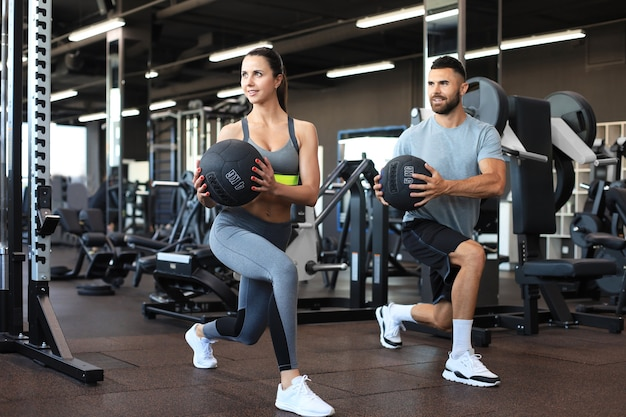 Schönes junges sportpaar trainiert mit medizinball in der turnhalle.