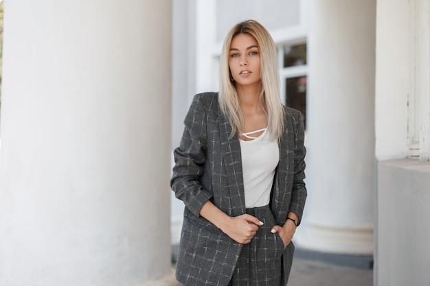 Schönes junges stilvolles modell blondes mädchen in einem vintage grauen mantel mit hose und einem weißen t-shirt auf der straße