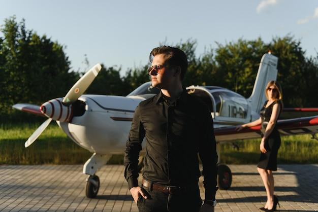 Schönes junges stilvolles paar in der offiziellen kleidung, die nahe privatflugzeug steht