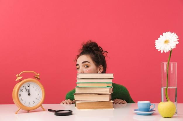 Schönes junges studentenmädchen, das am tisch lokalisiert, mit büchern studierend betrachtet, heraus schaut