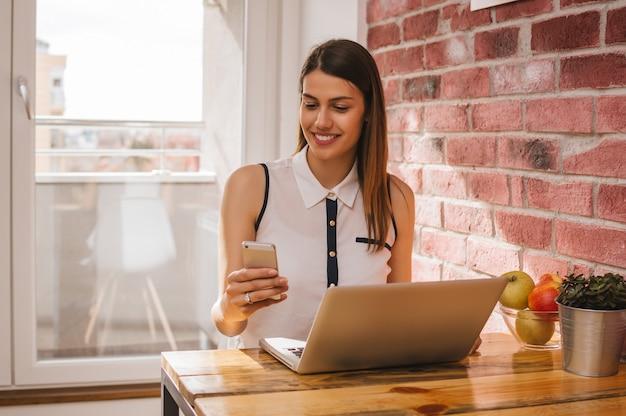 Schönes junges studentenmädchen, das zuhause telefon beim stydying auf laptop überprüft