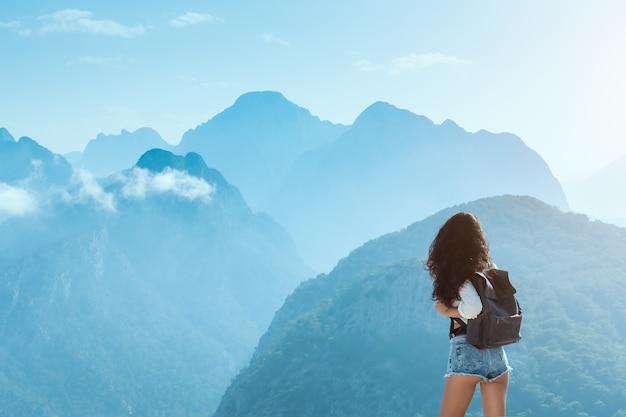 Schönes junges touristenmädchen mit rucksack an bergen