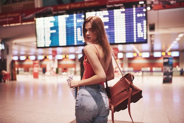 Schönes junges touristenmädchen mit rucksack im internationalen flughafen, nahe fluginformationstafel