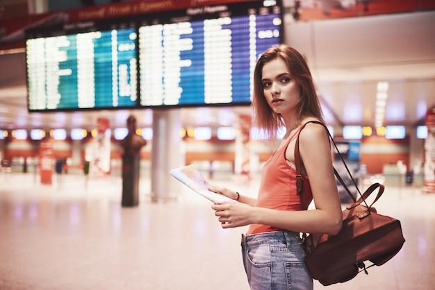 Schönes junges touristenmädchen mit rucksack im internationalen flughafen