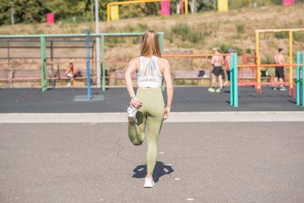 Schönes, junges und sportliches mädchen streckt ihre beine auf dem straßensportplatz aus