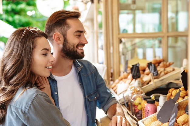 Schönes junges verliebtes paar, das draußen auf der stadtstraße spazieren geht und lebensmittel kauft