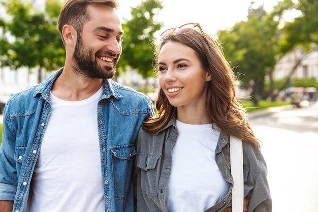 Schönes junges verliebtes paar, das draußen auf der stadtstraße spazieren geht und sich umarmt