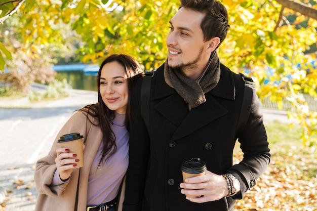 Schönes junges verliebtes paar, das im herbst zeit zusammen im park verbringt, sich umarmt, kaffeetassen zum mitnehmen hält