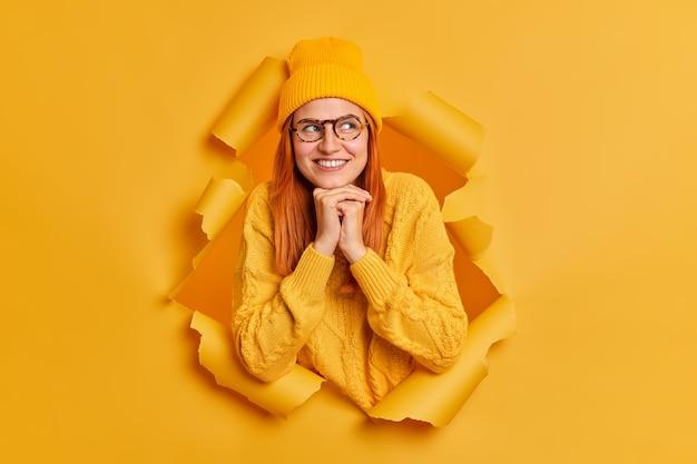 Schönes junges weibliches model mit roten haaren hält die hände unter dem kinn konzentriert beiseite und lächelt sanft, trägt modische jugendkleidung, denkt über zukünftige pläne nach und stellt sich etwas gutes vor.