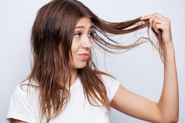 Schönes junges weibliches modell kümmert sich um ihr haar und benutzt einen haarglätter