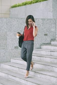 Schönes karrieremädchen, welches die treppe hinuntergeht, die am telefon spricht