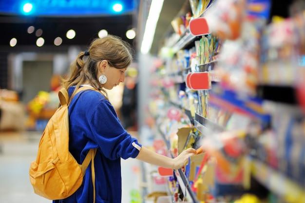Schönes kaufendes lebensmittel der jungen frau am supermarkt