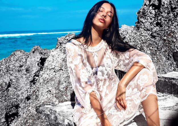 Schönes kaukasisches frauenmodell mit dunklem langem haar im transparenten weißen langen blusenkleid, das nahe felsen und blauem himmel und ozean aufwirft
