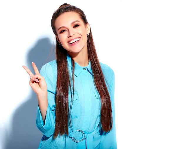 Schönes kaukasisches lächelndes brunettefrauenmodell im stilvollen kleid des hellen blauen sommers lokalisiert auf weißem hintergrund. zeige friedenszeichen