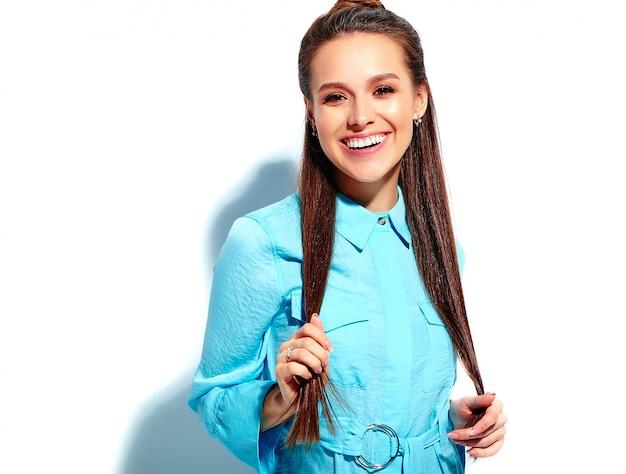 Schönes kaukasisches lächelndes brunettefrauenmodell im stilvollen kleid des hellen blauen sommers lokalisiert auf weißem hintergrund