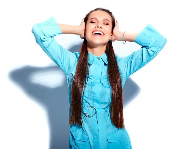 Schönes kaukasisches lächelndes brunettefrauenmodell im stilvollen kleid des hellen blauen sommers