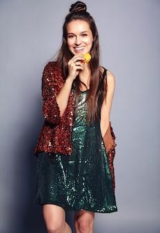 Schönes kaukasisches lächelndes hipster-brünettenfrauenmodell in der hellen glänzenden reflektierenden sommerlichen stilvollen jacke und im grünen kleid, die auf grau aufwerfen. französische makrone essen